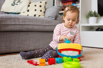 Two years old toddler girl playing on the floor, putting plastic shapes into the box with appropriate holes, focus on the toy