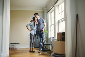 Young couple embracing while decorating home.