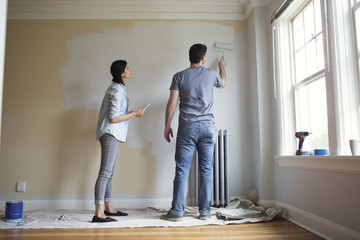 Young couple painting wall in new home.