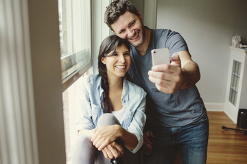 Young couple taking selfie in new home.