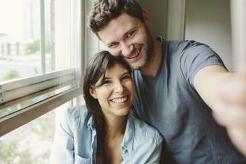 Young couple smiling and posing for selfie in new home.