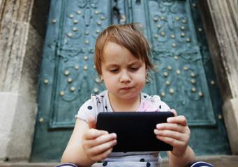 Social Media addiction. Little child girl  holding phone (psychological problems, media mania, education)