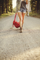 Woman carrying red backpack walking along rural road, low section.
