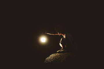Woman in cave with torch light.