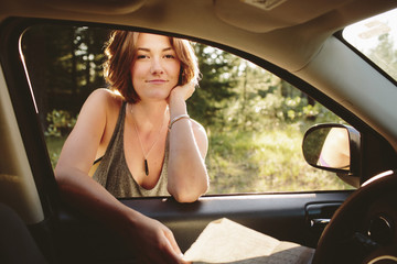 Woman leaning on car and looking at camera through window.