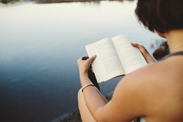 Woman sitting by lake reading book.