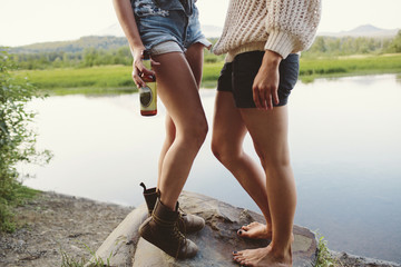 Two women standing by lake, one holding beer, low section