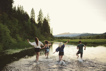 Four people running and splashing in lake.