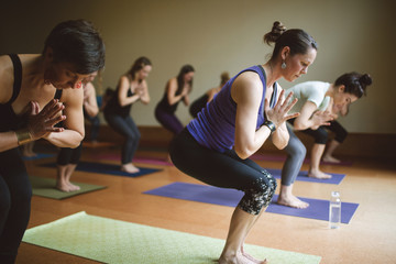 Women in yoga pose in yoga class.