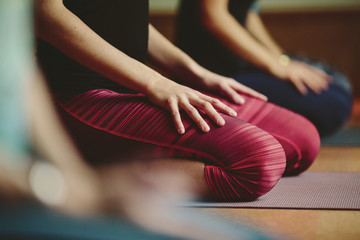 People kneeling on yoga mat in yoga class.