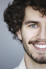 Cropped portrait of man with beard smiling toward camera.