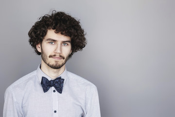 Man with curly hair and bow tie, studio shot.