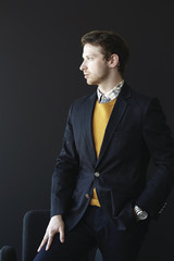 Man wearing suit jacket and mustard sweater.