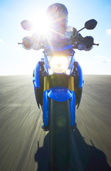 Person riding motorbike towards camera in sunlight.