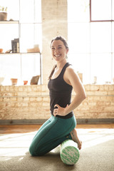Smiling woman kneeling in sportswear doing pilates exercises.