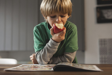 Boy sitting at table, reading book, eating apple
