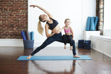 Woman doing yoga, young daughter sitting on her leg