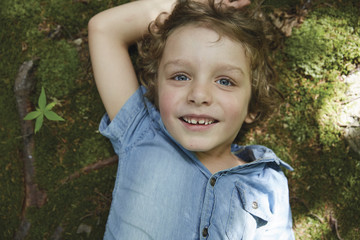 Portrait of boy, lying on grass, overhead view