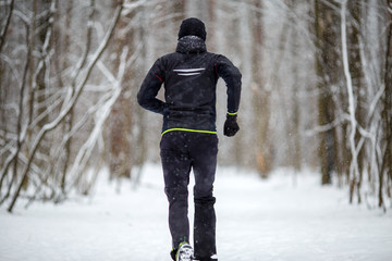 Image from back of man in sports clothes on run in winter