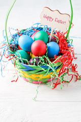 Image of basket with colorful eggs on empty blue background on wooden table