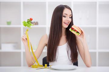 Diet. Dieting concept. Girl choosing healthy vs junk food.