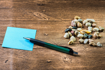 Pencil placed on post-it with many pebbles in wooden background