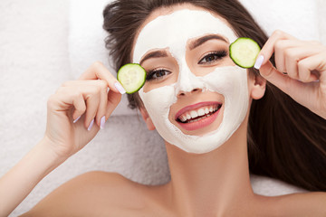 Spa. Attractive funny woman with a clay mask on her face.