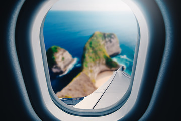 Wall Mural - Airplane is flying over blue sea. Tropical beach ocean landscape. View from plane window