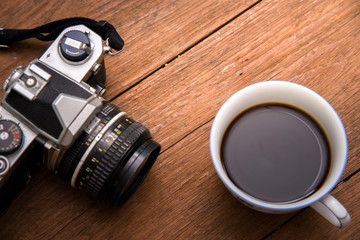 Coffee cup top view and camera on wooden vintage table background