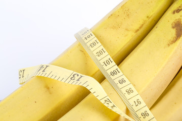 Ripe banana and measuring tape on the white background. Healthy lifestyle - fruit food, sport exercising.