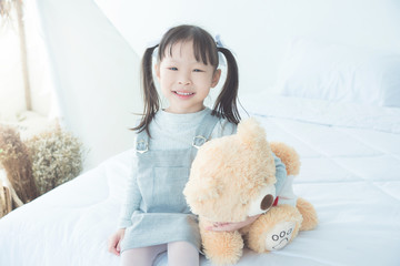 Little asian girl smiling while hugging stuffed bear on bed