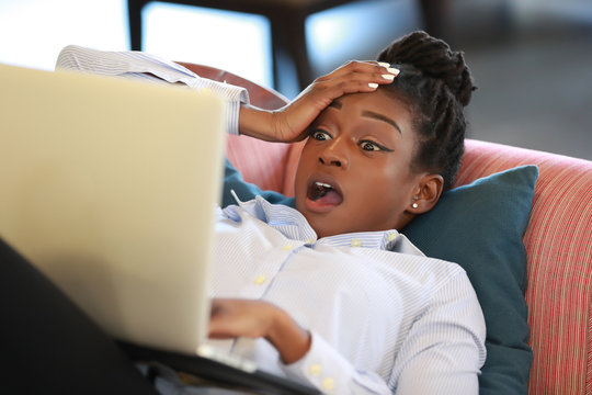 Woman watching laptop in disbelief