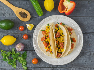 Three Mexican tacos on a plate with ingredients for cooking.