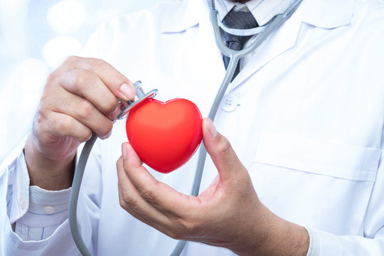 check up on a red heart ball on blur office in the hospital and bokeh background. Concept of health care.