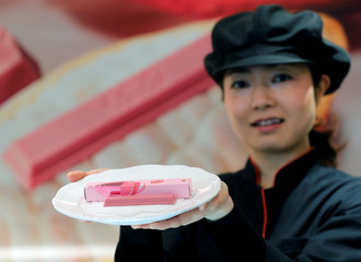 A staff poses with Nestle's KITKAT Chocolatory Sublime Ruby, made of pink 'Ruby' chocolate, on a plate during a photo opportunity at KITKAT Chocolatory shop in Tokyo