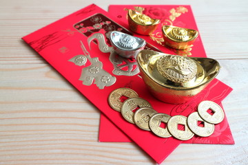 "Gold and money coin on red pocket "" Ang Pao"" with background wood table,Chinese word mean ""Happy"""