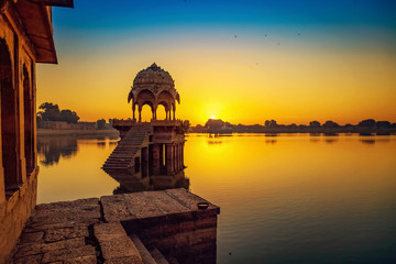 Wall Mural - Gadi Sagar Lake Jaisalmer Rajasthan with ancient architecture at sunrise.