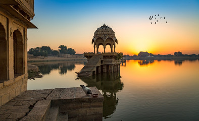 Wall Mural - Ancient architecture ruins at Gadi Sagar (Gadisar) lake Jaisalmer, Rajasthan at sunrise