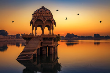 Ancient temple at Gadi Sagar (Gadisar) lake Jaisalmer Rajasthan, India at dawn. Fotomurales