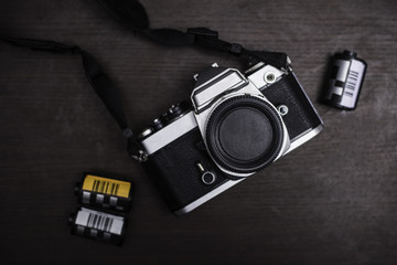 Vintage camera and film on wood background.