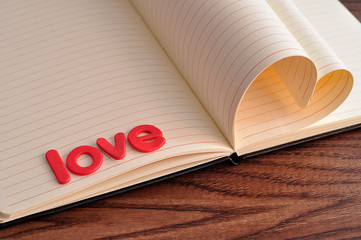 Pages of a book bend in a heart shape displayed with the word love
