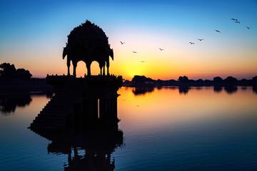 Fototapete - Gadi Sagar lake (Gadisar) at Jaisalmer, Rajasthan with ancient temple at dawn.