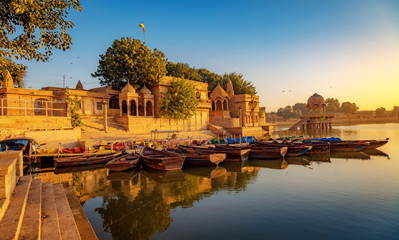 Wall Mural - Gadi Sagar (Gadisar) lake Jaisalmer Rajasthan with tourist boats and ancient architecture at sunrise.