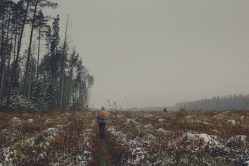Tourist walking through autumn field in Moscow Region, Russia.  Low contrast style