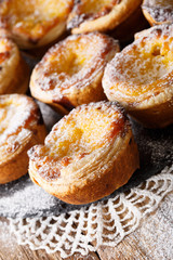 Portuguese dessert: Pastel de nata with powdered sugar close-up on the table. vertical