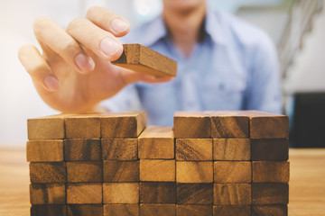 Risk and strategy wealth plan - man hand with wooden block thinking about value investment Fototapete