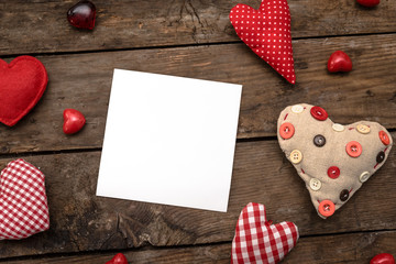 Preparations for Valentine's Day: a notebook for congratulation or sweet notes, gift, candy in the form of hearts, red ribbon and top view, copy space