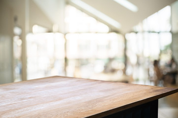 empty wooden desk over blurred montage coffee shop cafe / restaurant background