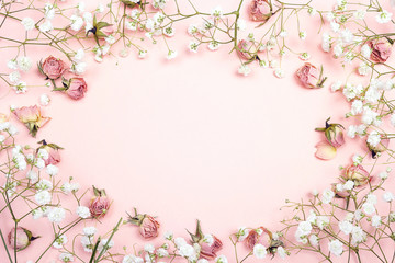 Frame of small delicate white flowers and roses on pink background. Place for text.