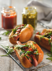 Delicious fresh hot dogs in homemade buns with arugula and ketchup on a wooden background.